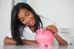 Χαμογελώντας επιχειρηματίας που βάζει τα νομίσματα στη piggy τράπεζα στο γραφείο της Στοκ εικόνα με δικαίωμα ελεύθερης χρήσης