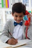 Χαμογελώντας επιχειρηματίας που γράφει μιλώντας στο τηλέφωνο γραμμών εδάφους Στοκ Εικόνες