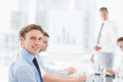 Χαμογελώντας επιχειρηματίας που εξετάζει τη κάμερα κατά τη διάρκεια μιας συνεδρίασης Στοκ φωτογραφία με δικαίωμα ελεύθερης χρήσης