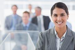 Χαμογελώντας επιχειρηματίας που εξετάζει τη κάμερα κατά τη διάρκεια της διάσκεψης Στοκ Φωτογραφία