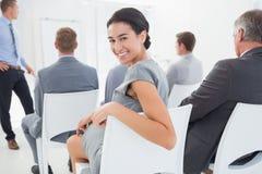 Χαμογελώντας επιχειρηματίας που εξετάζει τη κάμερα κατά τη διάρκεια της διάσκεψης Στοκ εικόνες με δικαίωμα ελεύθερης χρήσης