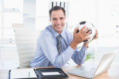 Χαμογελώντας επιχειρηματίας που εξετάζει τη κάμερα με τη σφαίρα ποδιών Στοκ Εικόνα