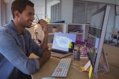 Χαμογελώντας επιχειρηματίας που εξετάζει τον υπολογιστή στην αρχή Στοκ Φωτογραφία