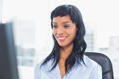 Χαμογελώντας επιχειρηματίας που εξετάζει τον υπολογιστή της Στοκ φωτογραφία με δικαίωμα ελεύθερης χρήσης