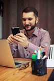 Χαμογελώντας επιχειρηματίας που εξετάζει το τηλέφωνό του Στοκ Εικόνες