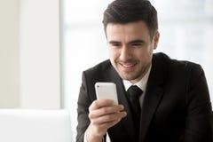 Χαμογελώντας επιχειρηματίας που εξετάζει το smartphone διαθέσιμο, χρησιμοποίηση κινητή Στοκ Εικόνα
