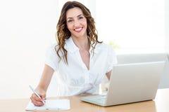 Χαμογελώντας επιχειρηματίας που εργάζεται με το lap-top της και τη λήψη των σημειώσεων Στοκ Εικόνες