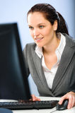 Χαμογελώντας επιχειρηματίας που εργάζεται στον υπολογιστή της Στοκ εικόνα με δικαίωμα ελεύθερης χρήσης