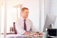 Χαμογελώντας επιχειρηματίας που εργάζεται στον υπολογιστή στοκ φωτογραφία με δικαίωμα ελεύθερης χρήσης