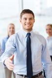 Χαμογελώντας επιχειρηματίας που καθιστά τη χειραψία στην αρχή Στοκ Φωτογραφία