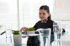 Χαμογελώντας επιχειρηματίας που κοιτάζει μακριά καθμένος στο γραφείο Στοκ εικόνες με δικαίωμα ελεύθερης χρήσης
