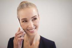 Χαμογελώντας επιχειρηματίας που κοιτάζει μακριά μιλώντας στο κινητό τηλέφωνο ενάντια στον τοίχο Στοκ φωτογραφίες με δικαίωμα ελεύθερης χρήσης