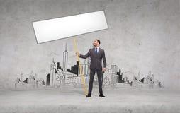 Χαμογελώντας επιχειρηματίας που κρατά το λευκό κενό χαρτόνι Στοκ εικόνες με δικαίωμα ελεύθερης χρήσης