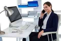 Χαμογελώντας επιχειρηματίας που μιλά στο κινητό τηλέφωνο στο γραφείο με τον υπολογιστή Στοκ Εικόνα