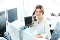Χαμογελώντας επιχειρηματίας που μιλά στο τηλέφωνο στην αρχή Στοκ φωτογραφίες με δικαίωμα ελεύθερης χρήσης