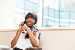 Χαμογελώντας επιχειρηματίας που μιλά στο τηλέφωνο στην αρχή Στοκ φωτογραφία με δικαίωμα ελεύθερης χρήσης