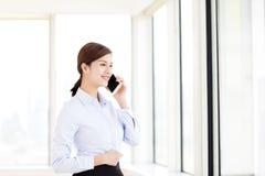 Χαμογελώντας επιχειρηματίας που μιλά στο τηλέφωνο στην αρχή Στοκ Φωτογραφία
