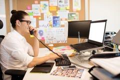 Χαμογελώντας επιχειρηματίας που μιλά στο τηλέφωνο στο δημιουργικό γραφείο Στοκ Εικόνα