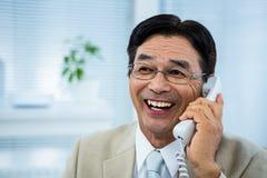 Χαμογελώντας επιχειρηματίας που μιλά στο τηλέφωνο Στοκ εικόνες με δικαίωμα ελεύθερης χρήσης