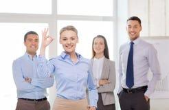 Χαμογελώντας επιχειρηματίας που παρουσιάζει εντάξει-σημάδι στην αρχή Στοκ Φωτογραφία
