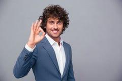 Χαμογελώντας επιχειρηματίας που παρουσιάζει εντάξει σημάδι Στοκ Εικόνες