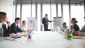Χαμογελώντας επιχειρηματίας που παρουσιάζει στους συναδέλφους στη αίθουσα συνδιαλέξεων φιλμ μικρού μήκους