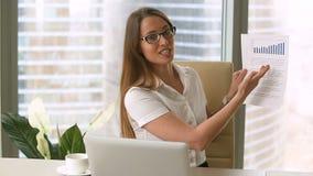 Χαμογελώντας επιχειρηματίας που παρουσιάζει το επιχειρησιακό έγγραφο, που παρουσιάζει διάγραμμα ανάπτυξης στη κάμερα φιλμ μικρού μήκους