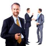 Χαμογελώντας επιχειρηματίας που στέκεται με τους συναδέλφους του Στοκ εικόνα με δικαίωμα ελεύθερης χρήσης