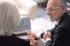 Χαμογελώντας επιχειρηματίας που συζητά το πρόγραμμα με το συνάδελφό του Στοκ φωτογραφία με δικαίωμα ελεύθερης χρήσης