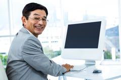 Χαμογελώντας επιχειρηματίας που χρησιμοποιεί τον υπολογιστή του Στοκ φωτογραφίες με δικαίωμα ελεύθερης χρήσης
