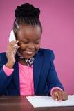 Χαμογελώντας επιχειρηματίας που χρησιμοποιεί το τηλέφωνο διαβάζοντας το έγγραφο Στοκ Εικόνες