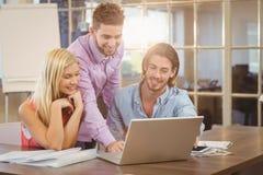 Χαμογελώντας επιχειρηματίας που χρησιμοποιεί το lap-top ενώ συνάδελφοι Στοκ Φωτογραφία