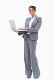 Χαμογελώντας επιχειρηματίας που χρησιμοποιεί το lap-top στεμένος Στοκ φωτογραφία με δικαίωμα ελεύθερης χρήσης
