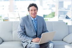 Χαμογελώντας επιχειρηματίας που χρησιμοποιεί το lap-top του στον καναπέ Στοκ Φωτογραφίες
