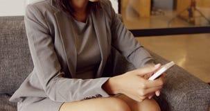 Χαμογελώντας επιχειρηματίας που χρησιμοποιεί το smartphone της στον καναπέ απόθεμα βίντεο