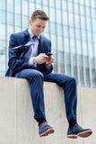 Χαμογελώντας επιχειρηματίας που χρησιμοποιεί το smartphone του Στοκ φωτογραφία με δικαίωμα ελεύθερης χρήσης