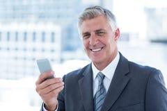 Χαμογελώντας επιχειρηματίας που χρησιμοποιεί το smartphone του Στοκ Εικόνα