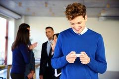 Χαμογελώντας επιχειρηματίας που χρησιμοποιεί το smartphone Στοκ Φωτογραφία