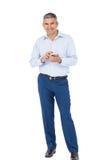 Χαμογελώντας επιχειρηματίας που χρησιμοποιεί το smartphone Στοκ φωτογραφία με δικαίωμα ελεύθερης χρήσης