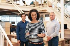 Χαμογελώντας επιχειρηματίας σε ένα γραφείο με τους συναδέλφους που στέκονται πίσω από την Στοκ Φωτογραφίες