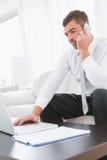 Χαμογελώντας επιχειρηματίας σε ένα τηλέφωνο με ένα lap-top στο σπίτι Στοκ Εικόνες