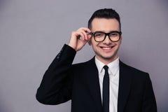 Χαμογελώντας επιχειρηματίας στα γυαλιά που εξετάζει τη κάμερα Στοκ Φωτογραφίες