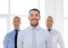 Χαμογελώντας επιχειρηματίας στην αρχή με την ομάδα στην πλάτη Στοκ Εικόνες