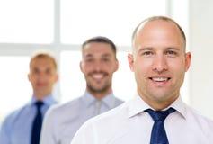 Χαμογελώντας επιχειρηματίας στην αρχή με την ομάδα στην πλάτη Στοκ φωτογραφία με δικαίωμα ελεύθερης χρήσης