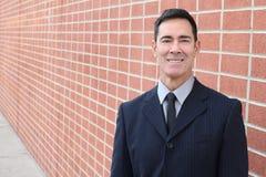 Χαμογελώντας επιχειρηματίας στο αστικό υπόβαθρο τουβλότοιχος με το διάστημα αντιγράφων στοκ εικόνα με δικαίωμα ελεύθερης χρήσης