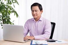 Χαμογελώντας επιχειρηματίας στο γραφείο του με το lap-top και έγγραφα σε δικοί του Στοκ Φωτογραφία
