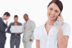 Χαμογελώντας επιχειρηματίας στο τηλέφωνο με τους συναδέλφους πίσω από την Στοκ εικόνα με δικαίωμα ελεύθερης χρήσης