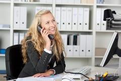 Χαμογελώντας επιχειρηματίας στο τηλέφωνο που ανατρέχει Στοκ φωτογραφία με δικαίωμα ελεύθερης χρήσης