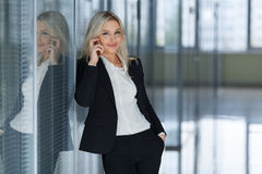 Χαμογελώντας επιχειρηματίας στο τηλέφωνο που εξετάζει τη κάμερα σε ένα γραφείο Στοκ φωτογραφία με δικαίωμα ελεύθερης χρήσης