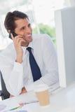 Χαμογελώντας επιχειρηματίας στο τηλέφωνο που εξετάζει τον υπολογιστή του Στοκ Εικόνες
